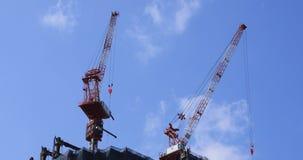 Grúas de mudanza en la construcción inferior detrás del cielo azul en Tokio almacen de metraje de vídeo