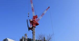 Grúas de mudanza en la construcción inferior detrás del cielo azul en Tokio metrajes