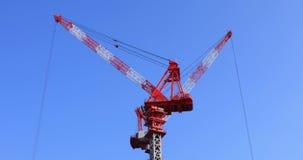Grúas de mudanza en la construcción inferior detrás del cielo azul en Tokio almacen de video