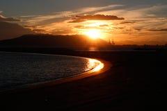 Grúas del puerto en la puesta del sol Fotografía de archivo libre de regalías