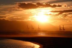 Grúas del puerto en la puesta del sol Fotos de archivo