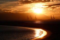 Grúas del puerto en la puesta del sol Imagenes de archivo