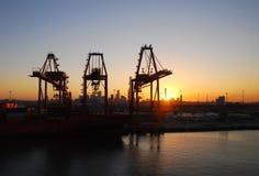 Grúas del puerto en la salida del sol Fotos de archivo
