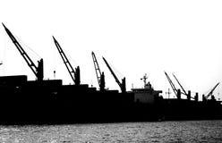 Grúas del puerto en silueta Fotos de archivo libres de regalías
