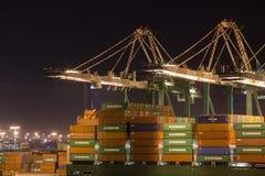 Grúas del puerto que hacen el trabajo del cargamento en la noche imagenes de archivo