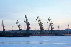 Grúas en el puerto, astillero por la tarde, en la puesta del sol foto de archivo