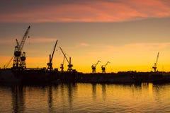 Grúas en la puesta del sol en el puerto de Riga imagen de archivo libre de regalías
