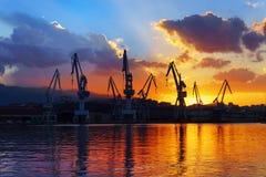 Grúas en Sestao en la puesta del sol Imagen de archivo