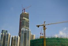 Grúas grandes al lado de altos edificios de la subida bajo construcción Foto de archivo libre de regalías