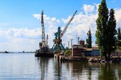 Grúas pesadas en puerto del cargo en riverbank fotos de archivo libres de regalías