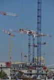 Grúas y sitio de construcción contra un cielo azul Foto de archivo