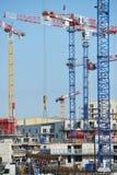 Grúas y sitio de construcción contra un cielo azul Imágenes de archivo libres de regalías