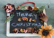 Grüße der frohen Weihnachten auf Tafel mit Weihnachten blüht Stockfotos