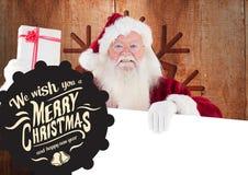 Grüße der frohen Weihnachten gegen Weihnachtsmann, der Geschenk und Plakat hält Lizenzfreie Stockfotografie