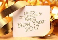 Grüße der frohen Weihnachten u. des guten Rutsch ins Neue Jahr mit Golddekorationen Stockbild