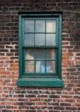 Grün gemaltes Fenster auf Backsteinmauer Lizenzfreie Stockbilder