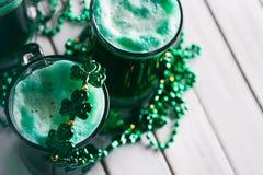 Grün: Grünes Bier mit Shamrock-Halskette für St Patrick Tag Lizenzfreies Stockbild