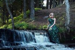 Grün kleidete junge Nymphenfrau nahe Wasserfall im Wald Stockbilder