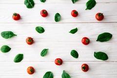 Grün lässt Spinats- und Kirschtomatenrahmen auf weißem Hintergrund Lizenzfreie Stockbilder