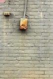 Grün malte alte Backsteinmauer mit Schaltkasten und Knopf Lizenzfreie Stockbilder