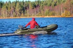 Grün, Motorboot, aufblasbares Gummiboot mit Motor auf hölzernem See lizenzfreies stockbild