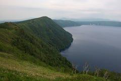 Grün neigt sich, den schönen und tiefen blauen See Mashu umgebend Stockfoto