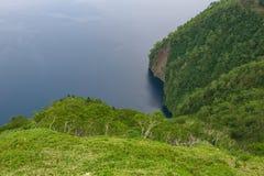 Grün neigt sich, den schönen und tiefen blauen See Mashu umgebend Stockfotografie