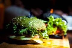 Grün, Schwarzminiburger mit Gemüse lizenzfreies stockbild