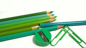 Grün tont Büroklammern, farbige Bleistifte und Bleistiftspitzer auf weißem Hintergrund Stockfoto