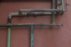 Grün und Aqua Rusty Pipes auf Coral Stucco Wall lizenzfreies stockbild