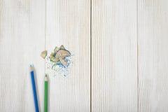 Grün und Blau färbte Bleistifte mit seinen Schnitzeln auf hölzerner Planke Stockfotos