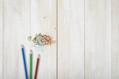 Grün und Blau färbte Bleistifte mit seinen Schnitzeln auf hölzerner Planke Lizenzfreie Stockfotografie