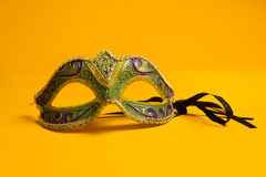 Grün und Gold Mardi Gras, venetianische Maske auf gelbem Hintergrund stockfoto