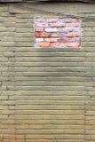 Grün und Ocker malten alte Backsteinmauer mit einem Flecken des neuen Ziegelsteines Lizenzfreie Stockbilder