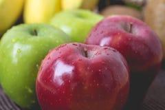Grün und Rot von Äpfeln auf schwarzem Gewebehintergrund Lizenzfreie Stockfotos