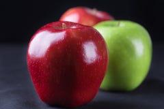 Grün und Rot von Äpfeln auf schwarzem Gewebehintergrund Stockfotografie