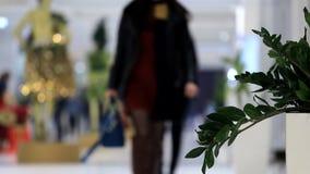 Grün verlässt vor dem hintergrund der gehenden Leute im Einkaufszentrum stock video