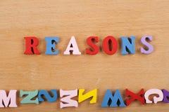GRÜNDE fassen auf dem hölzernen Hintergrund ab, der von den hölzernen Buchstaben des bunten ABC-Alphabetblockes verfasst wird, ko Stockbild
