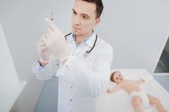 Gründlicher ausgezeichneter Kinderarzt, der Immunisierungseinspritzung vorbereitet Stockbilder