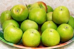 Grüne Äpfel auf einer Platte Stockfotos