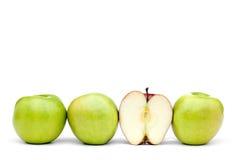 Grüne Äpfel mit einem einzelnen gegessenen roten Apfel Stockfoto