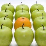 Grüne Äpfel mit einer Orange Lizenzfreie Stockfotos