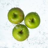 Grüne Äpfel mit Wasserspritzen stockfoto