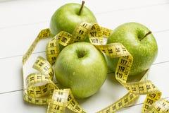 Grüne Äpfel und messendes Band stockfotos