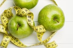 Grüne Äpfel und messendes Band lizenzfreie stockfotos