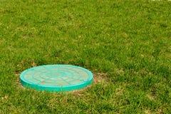 Grüne Abwasserkanalluke auf grünem Gras Stockfotografie