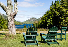 Grüne Adirondack-Stühle, die See übersehen Stockfotografie