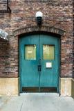 Grüne alte Holztür mit einer Backsteinmauer Stockfotos