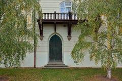 Grüne alte Tür mit hölzernem Balkon und Fenster und grüne Birke Stockbilder