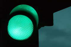 Grüne Ampel bis zum Nacht und bewölkter Himmel am Hintergrund Lizenzfreie Stockfotografie